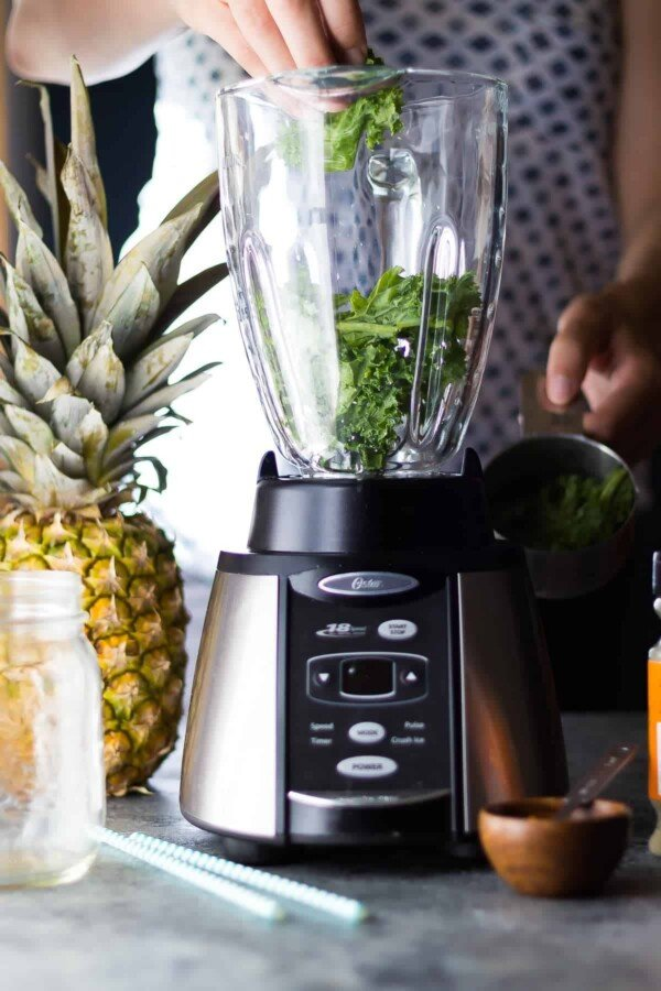 placing ingredients for breakfast smoothies into a blender