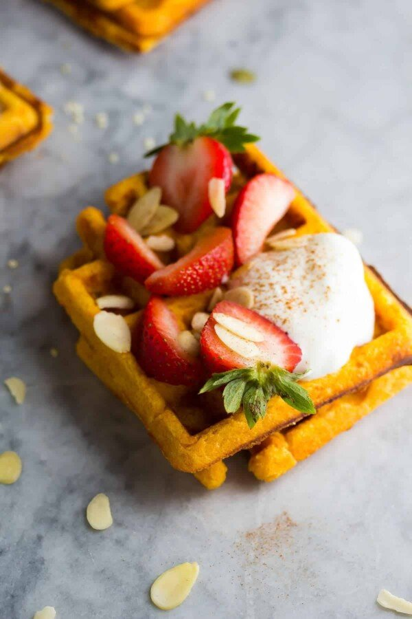 two sweet potato waffles with cream, almonds and strawberries