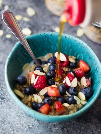 blue bowl with berry almond breakfast quinoa and syrup being drizzled onto it