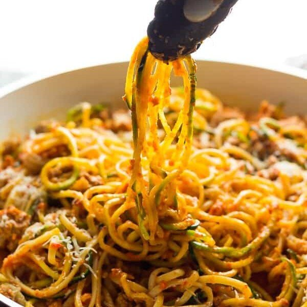 Tongs taking out ground turkey pasta in Romesco Sauce from white bowl