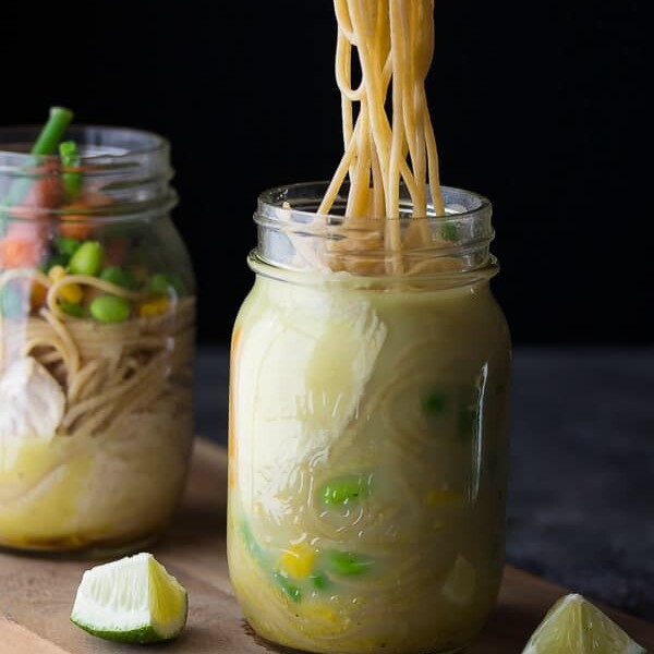 two mason jars with thai coconut instant noodles and lime wedges