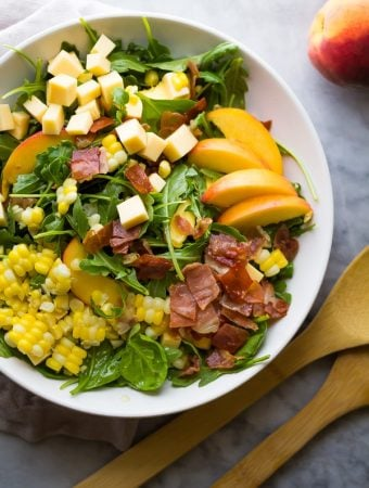 overhead shot of peach corn arugula salad in large white bowl with wooden tongs
