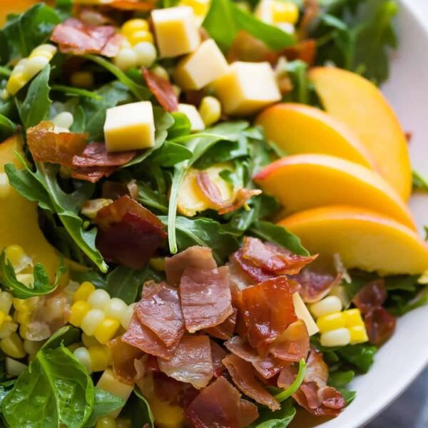 peach corn arugula salad in large white bowl