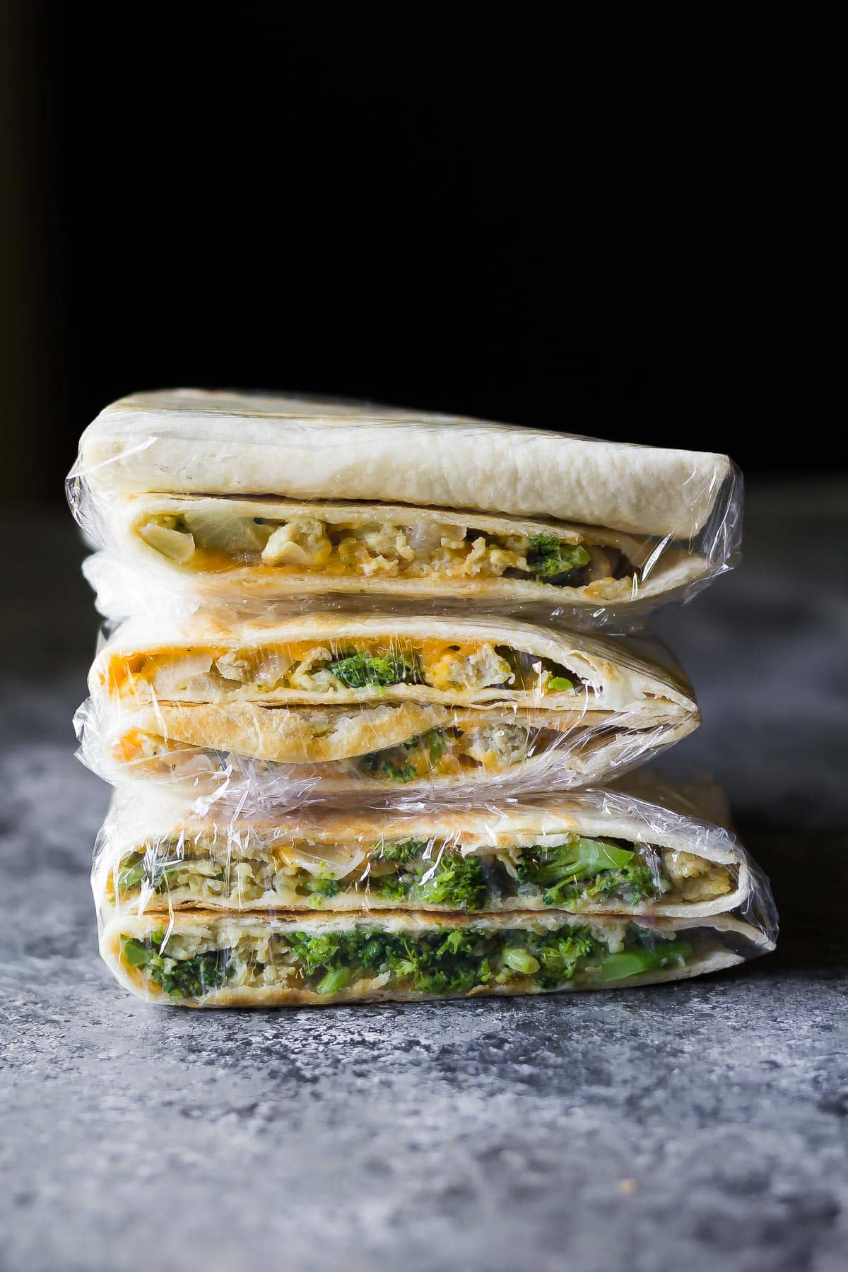 stack of Broccoli Cheddar Breakfast Quesadillas wrapped in plastic, ready for the freezer