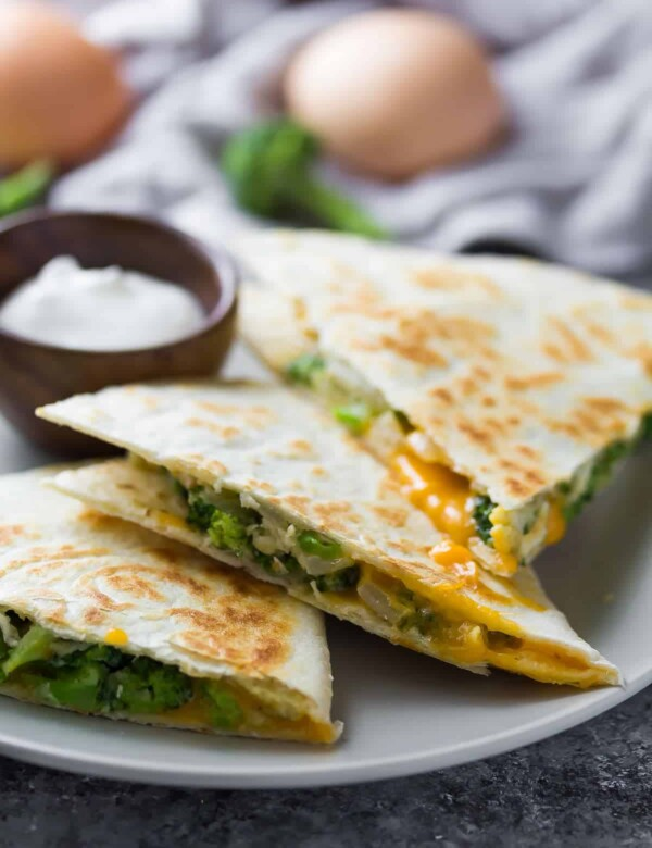 three triangle pieces of broccoli cheddar breakfast quesadilla on gray plate
