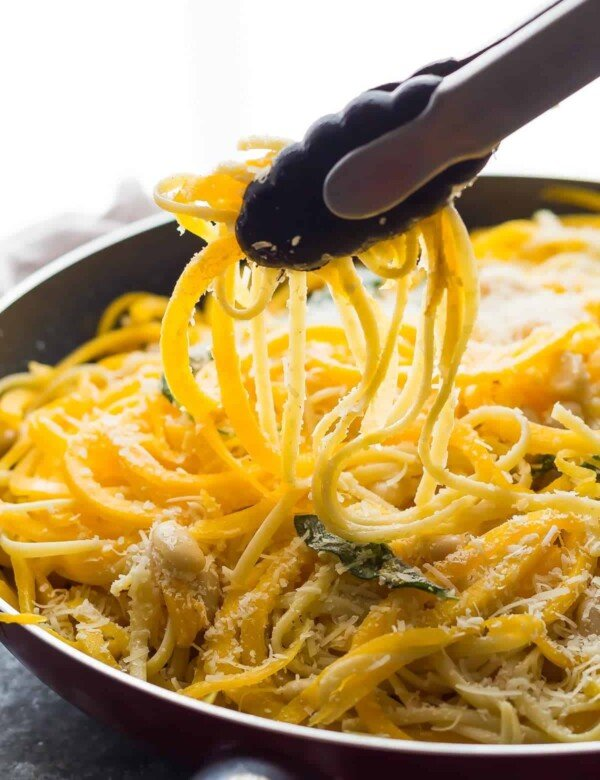 Close up shot of tongs taking out butternut squash noodles from large bowl