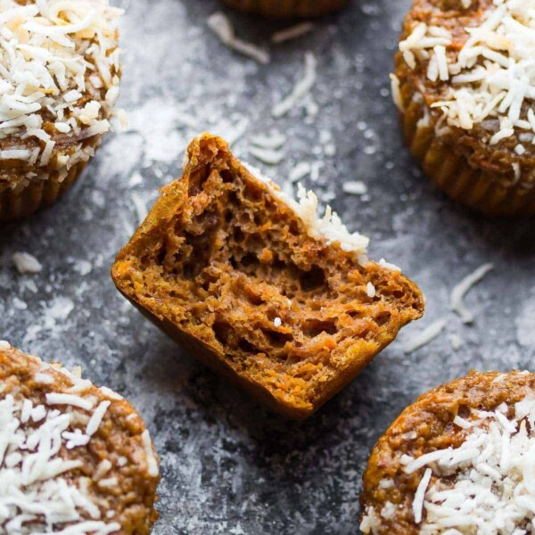 Carrot lentil protein muffins with a bite taken out of one on gray background