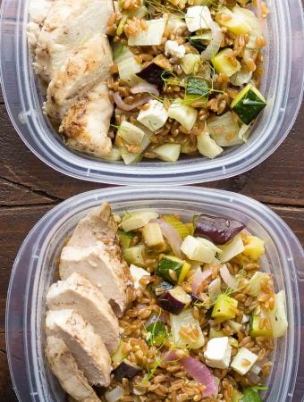 overhead shot of two plastic containers filled with mediterranean farro chicken lunch bowls