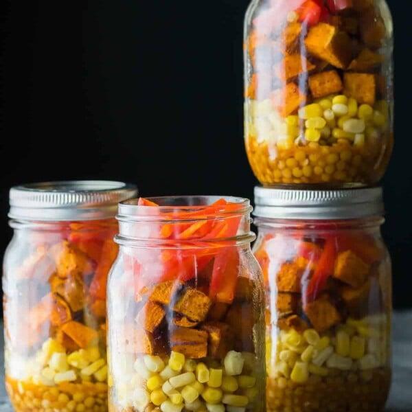 four mason jars filled with southwestern lentil sweet potato lunch bowls