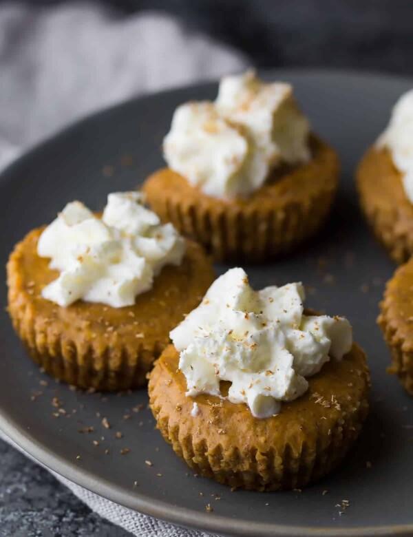 mini pumpkin greek yogurt cheesecakes sitting on dark gray plate