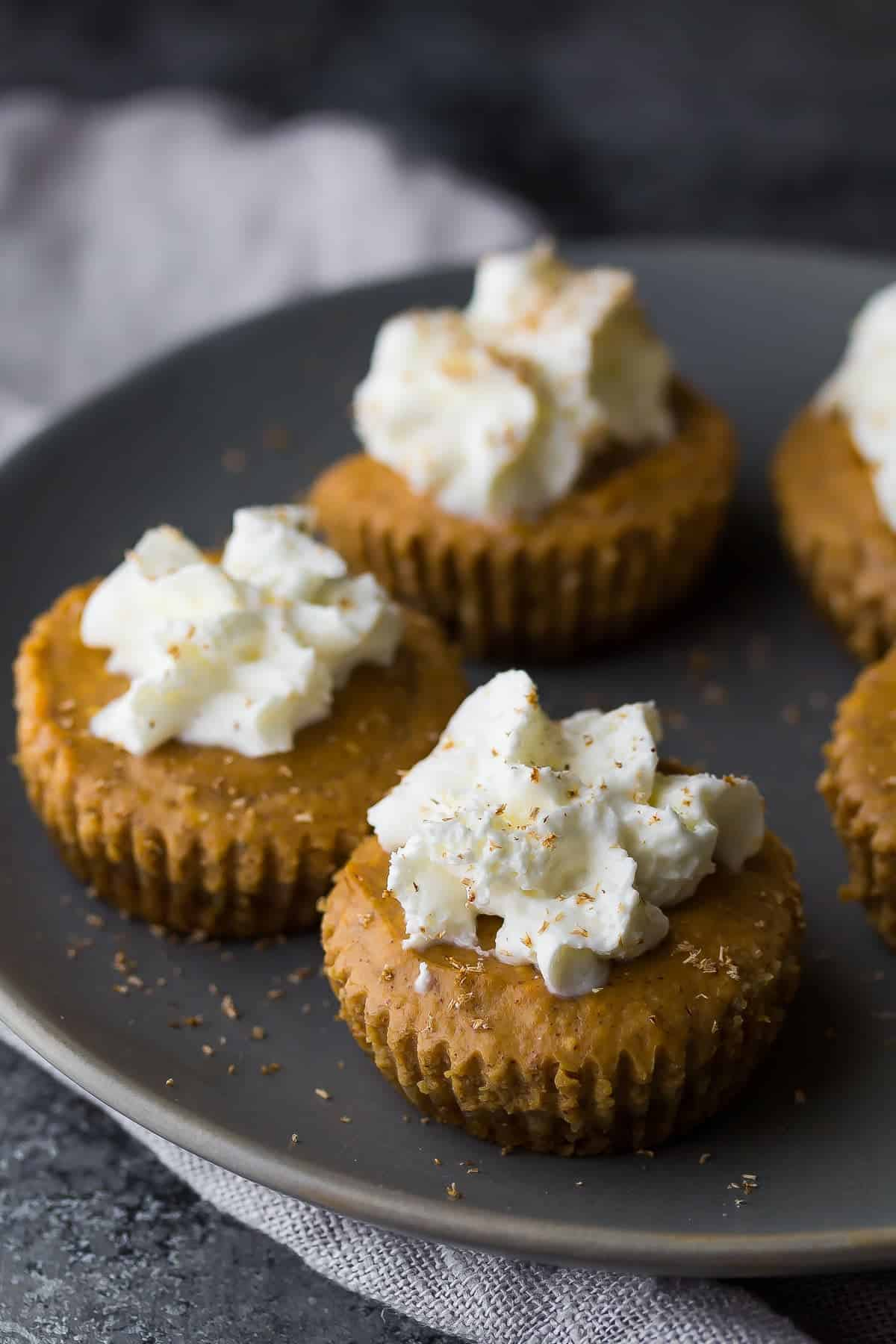mini pumpkin greek yogurt cheesecakes on plate with whipped cream on top