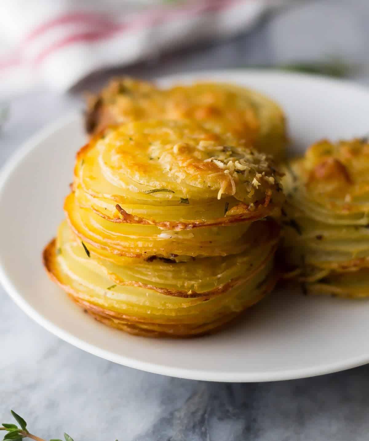 plate with three herb and garlic potato stacks