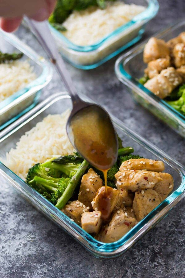 spoon drizzling sauce over honey sesame chicken lunch bowls