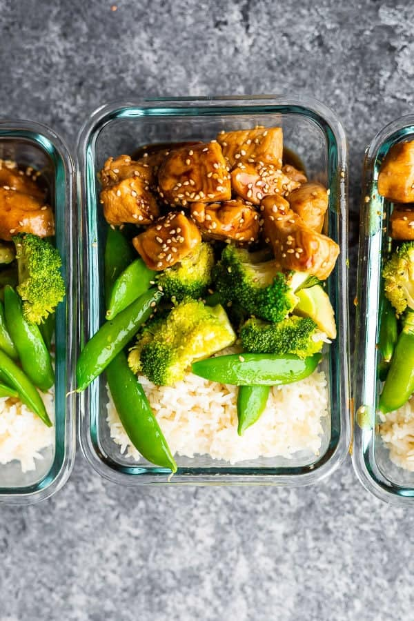 overhead shot of glass meal prep containers filled with honey sesame chicken lunch bowls