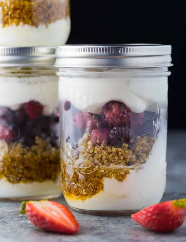 close up shot of berry breakfast parfaits in two mason jars with strawberries