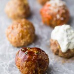 five baked turkey meatballs lined up on parchment paper