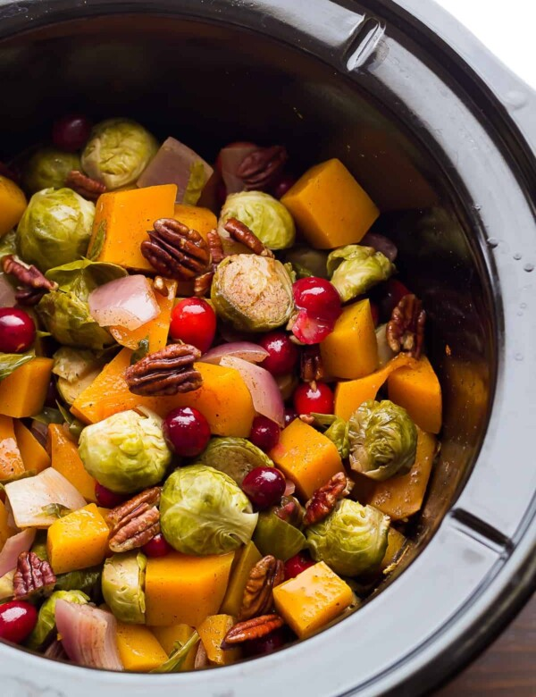 slow cooker filled with brussels sprouts cranberries butternut squash and pecans
