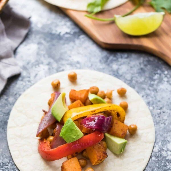 white plate with chickpea butternut squash fajitas on gray counter with fresh avocado and lime