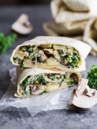 breakfast burrito with kale and mushrooms cut i half on parchment with fresh kale next to it