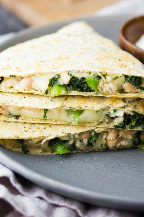 white bean kale quesadillas on gray plate with sour cream