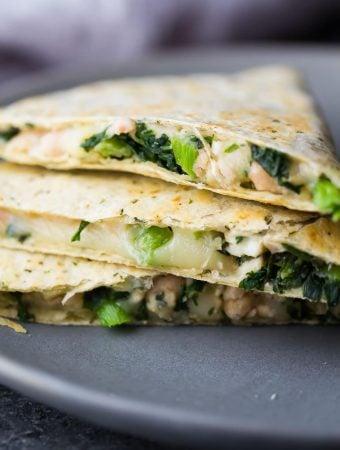 stack of three white bean kale quesadillas on gray plate