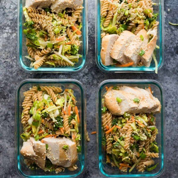 four glass containers with sesame chicken pasta salad lunch bowls