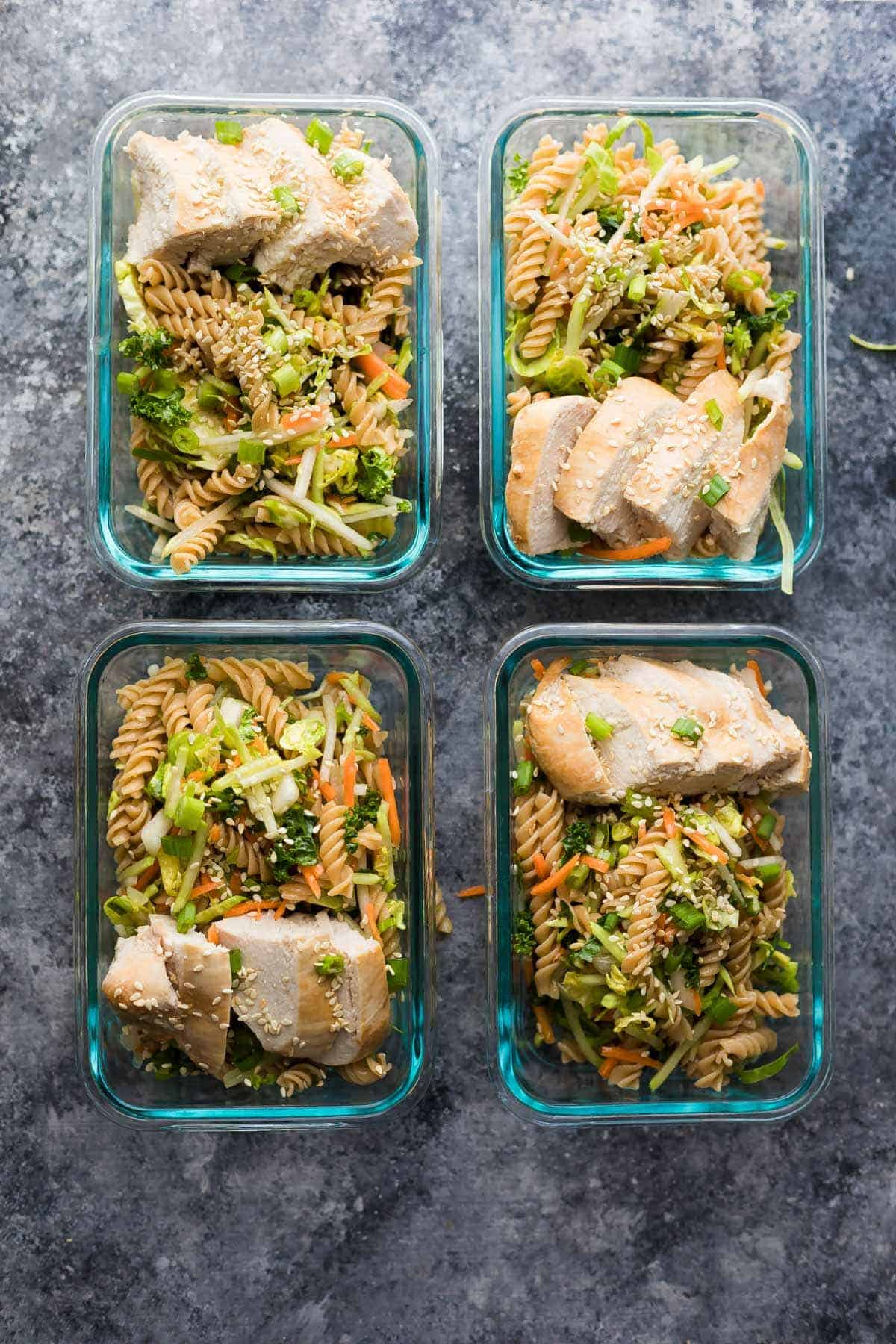 overhead view of four glass containers with Sesame Chicken Pasta Salad