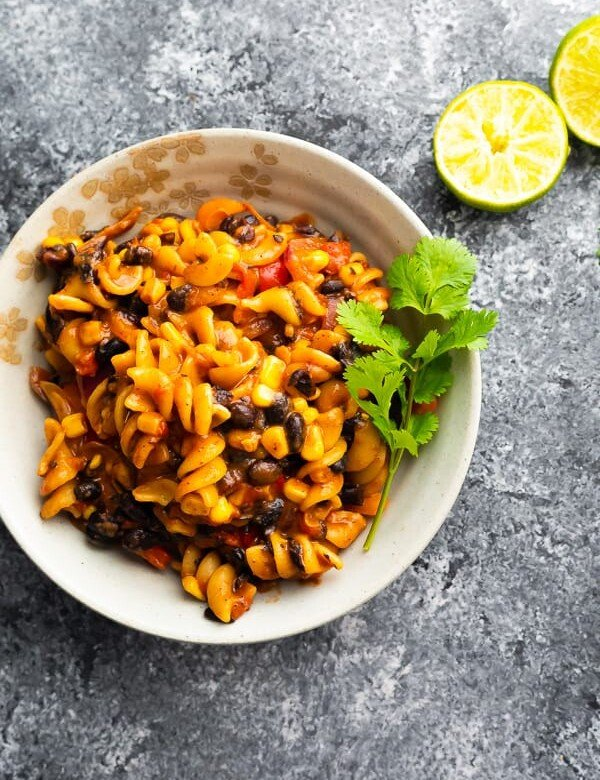 overhead shot of black bean fajita pasta in white bowl with parsley sprig and limes