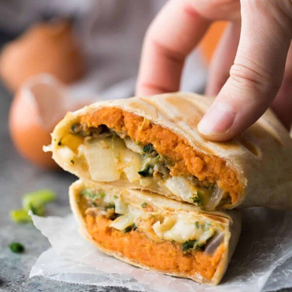 hand holding a sweet potato breakfast burrito cut in half on parchment