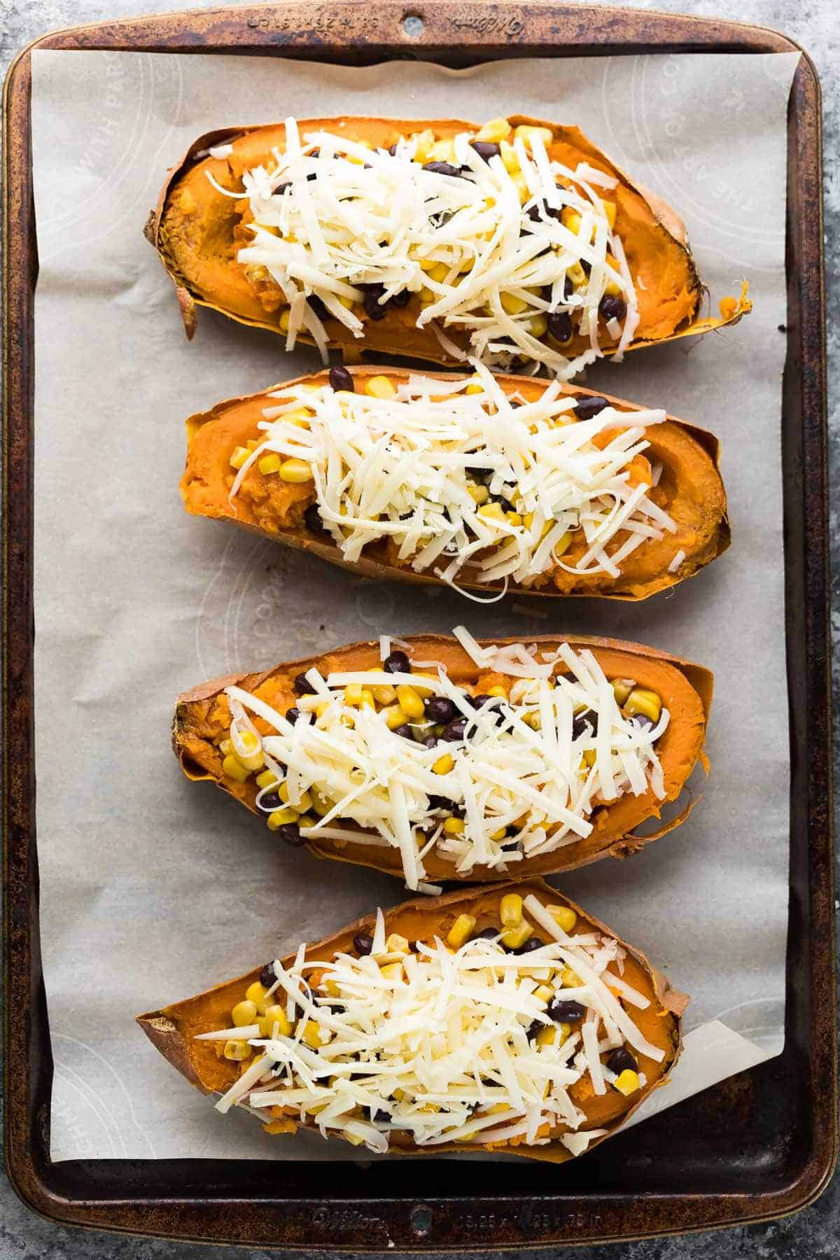 Overhead view of four Enchilada Stuffed Sweet Potatoes with cheese on a lined baking sheet