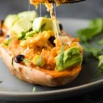 enchilada stuffed sweet potato on gray plate with fork taking a bite