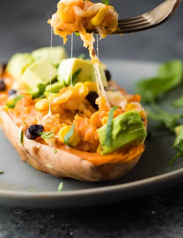 enchilada stuffed sweet potato on gray plate with fork taking a bite