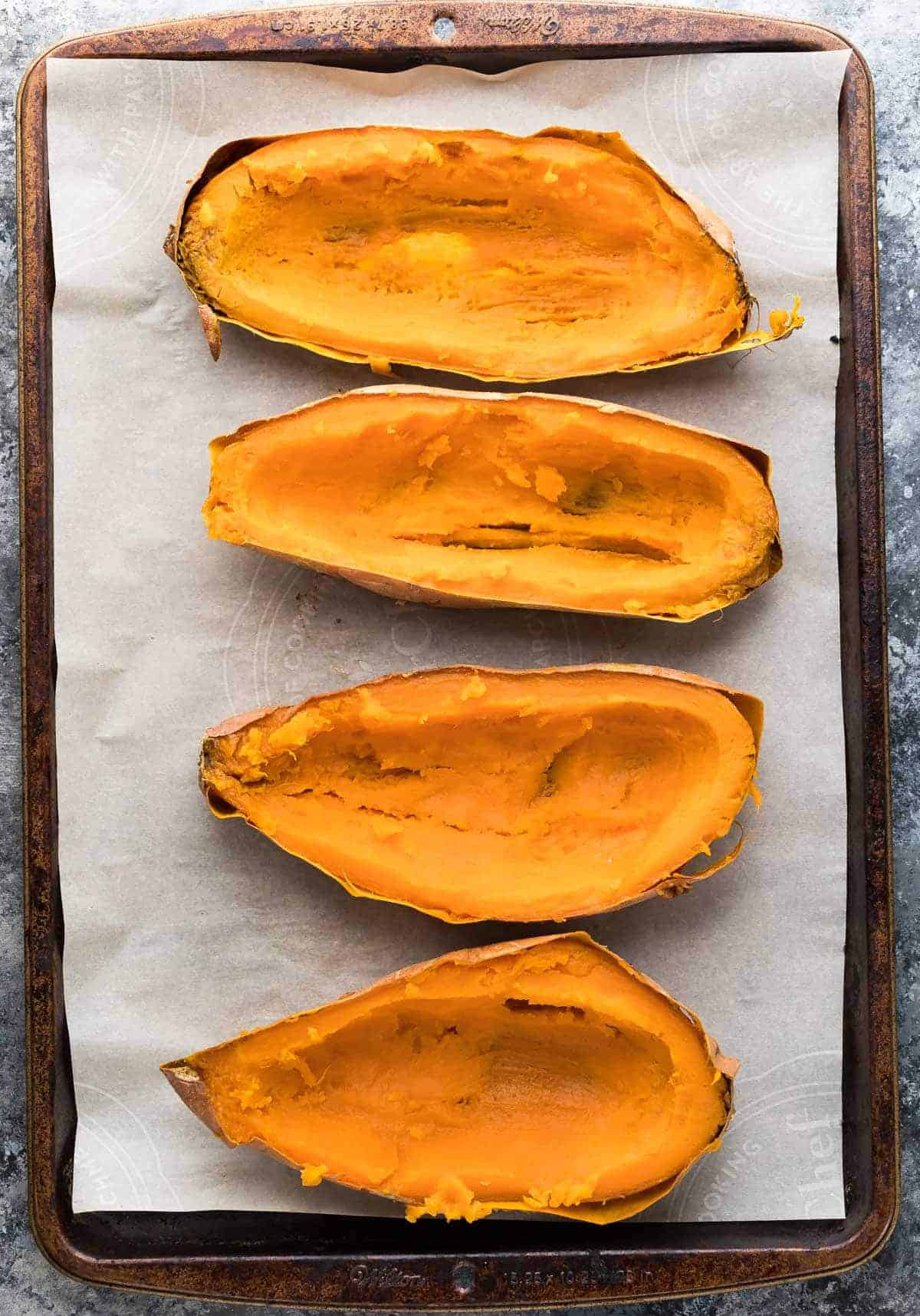 overhead view of four halved sweet potatoes on a lined baking sheet