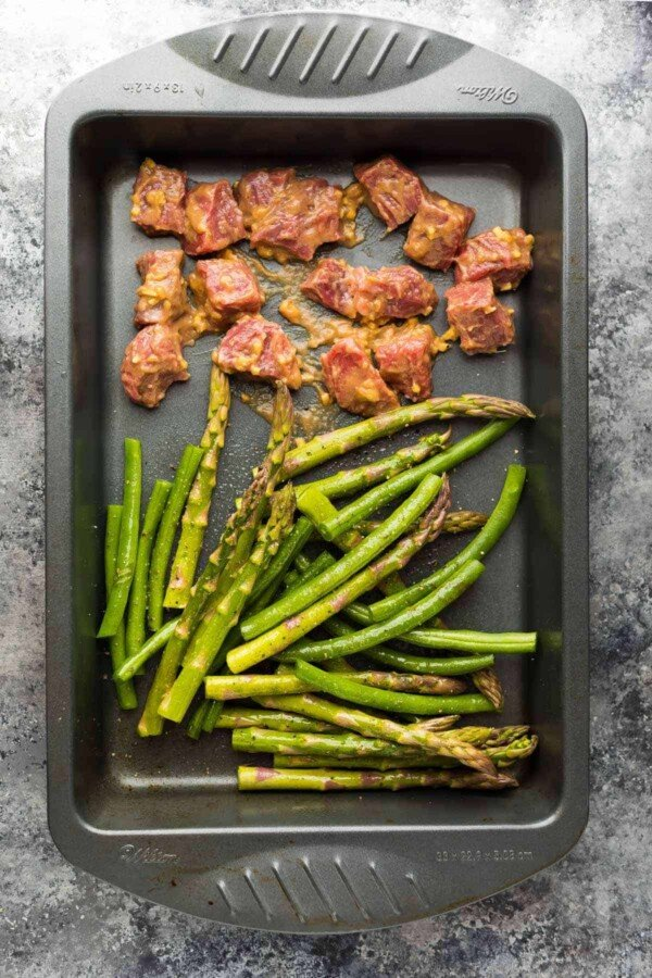 Hoisin Ginger steak cubes and cut asparagus and green beans in baking pan