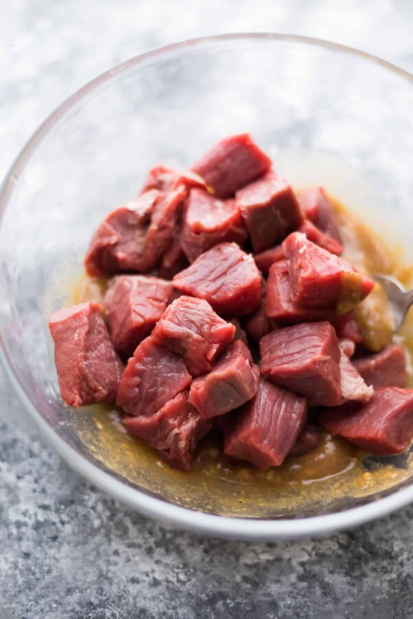 raw cubes of steak in hoisin ginger marinade in glass bowl