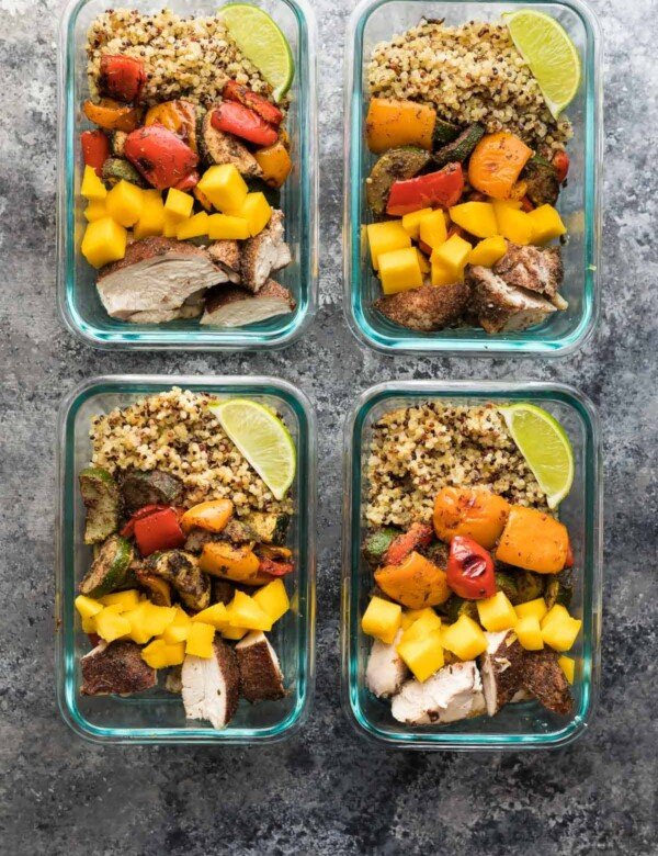 four glass meal prep containers with jamaican chicken quinoa lunch bowls