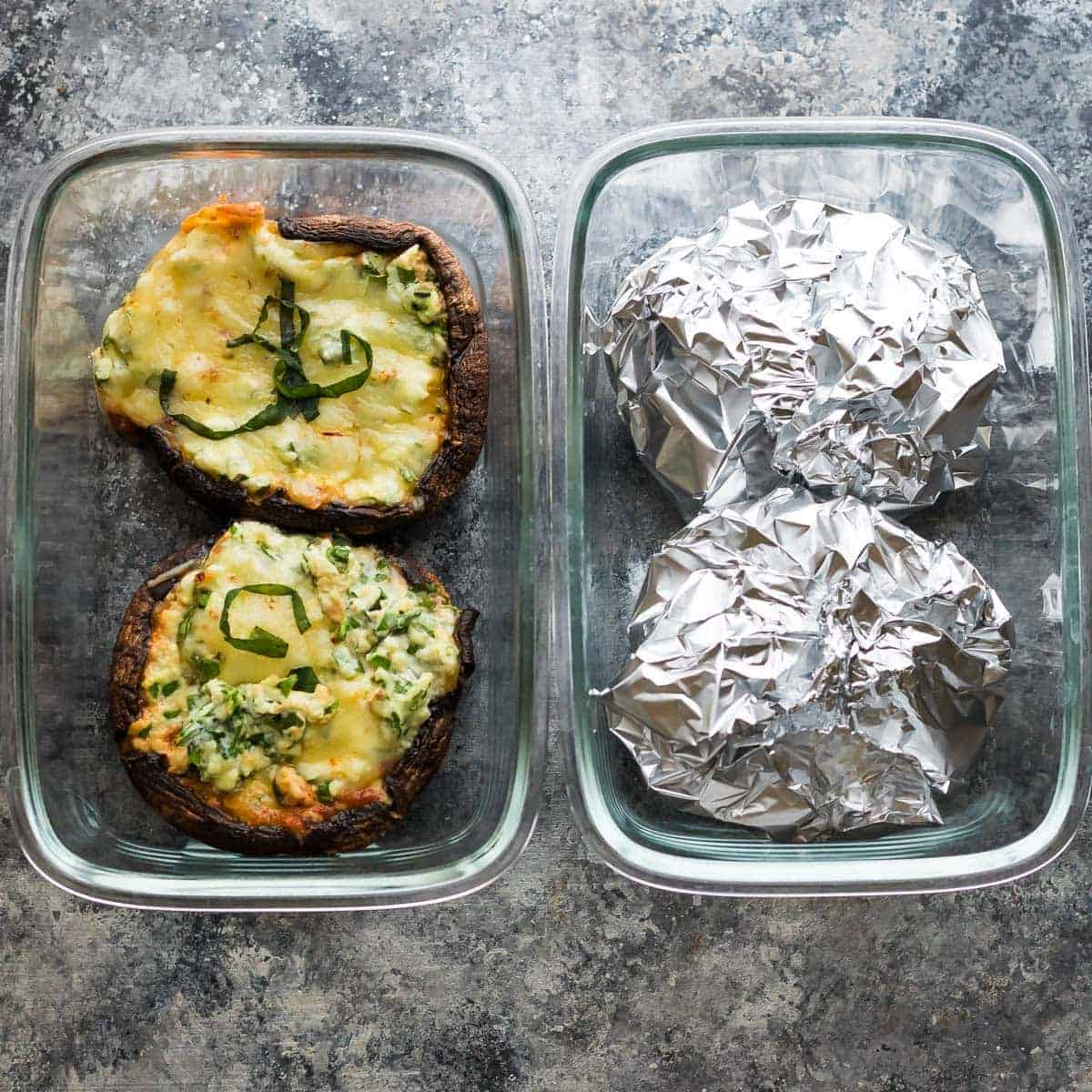 overhead shot of four lasagna stuffed portobello mushrooms with two of them enclosed in tinfoil