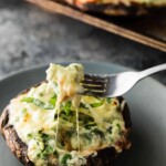 lasagna stuffed portobello mushroom on gray plate with fork taking a bite