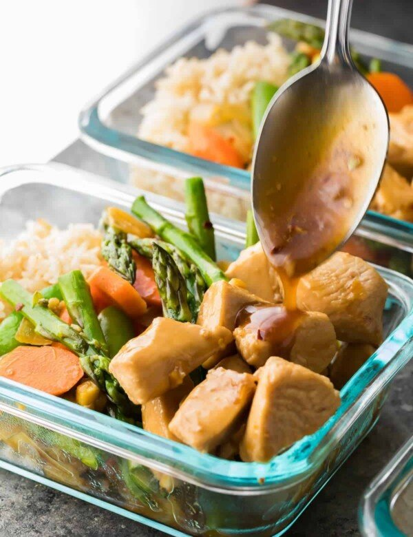 glass meal prep container with maple ginger chicken bowl and spoon drizzling the dressing