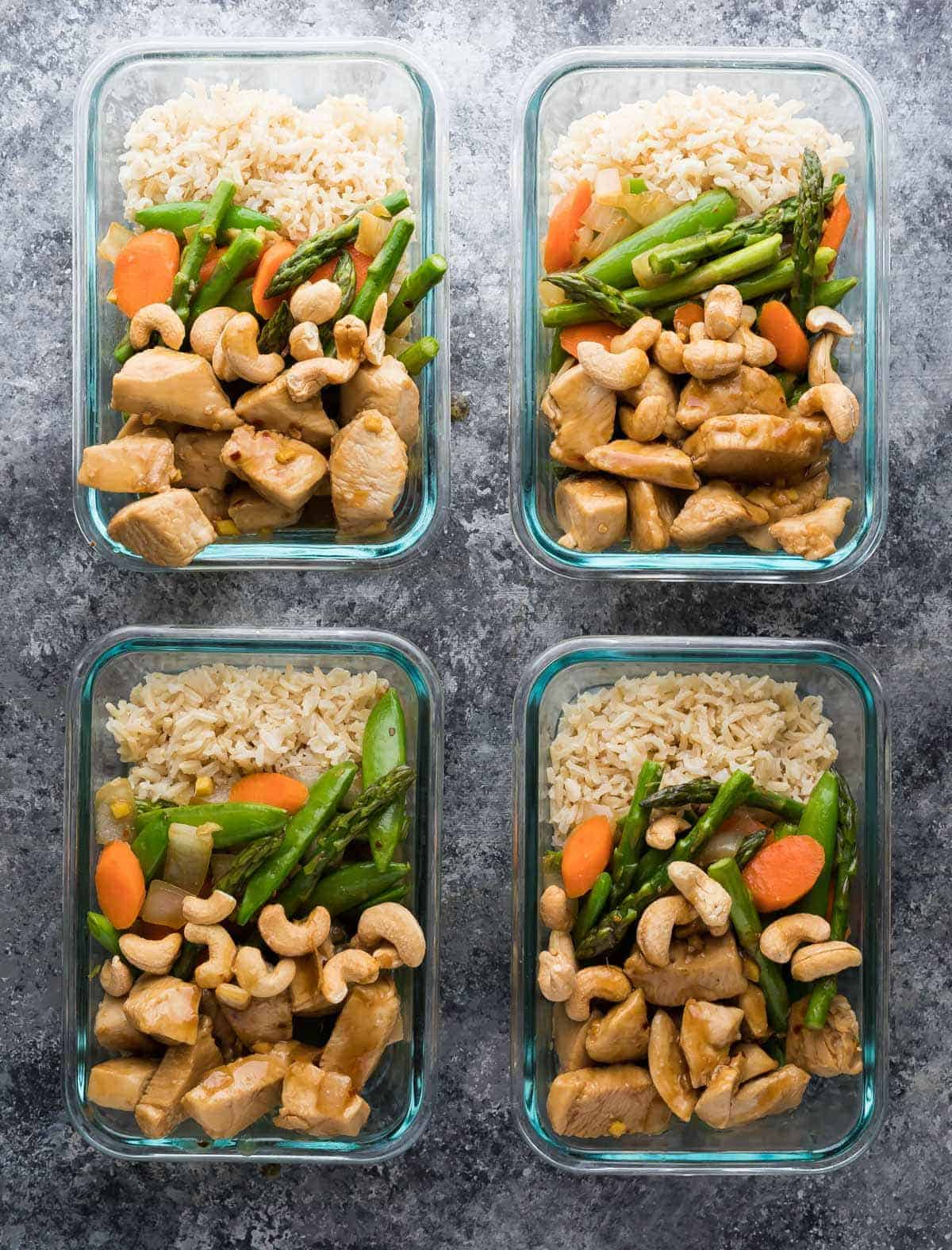 Overhead view of four maple ginger chicken meal prep lunch bowls in glass containers
