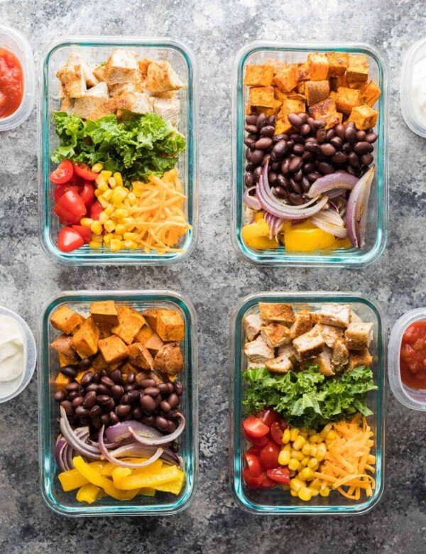 overhead shot of four glass meal prep containers with mix and match burrito bowls