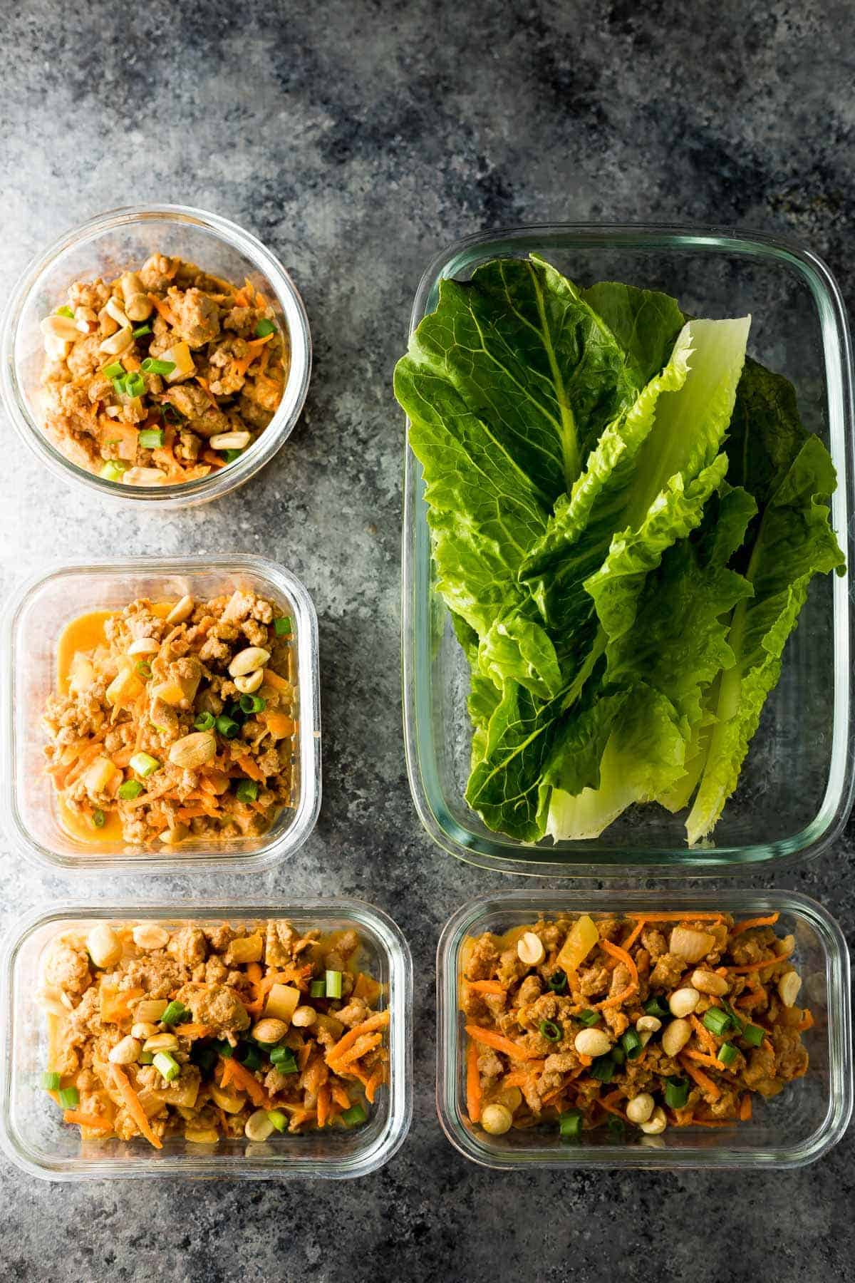 Ground turkey filling and romaine lettuce leaves in meal prep containers for thai turkey lettuce wrap recipe