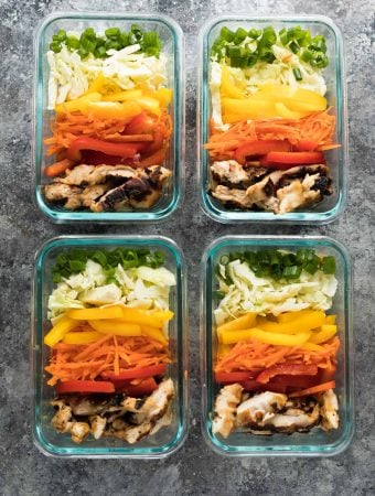 four glass meal prep containers with satay chicken lunch bowls