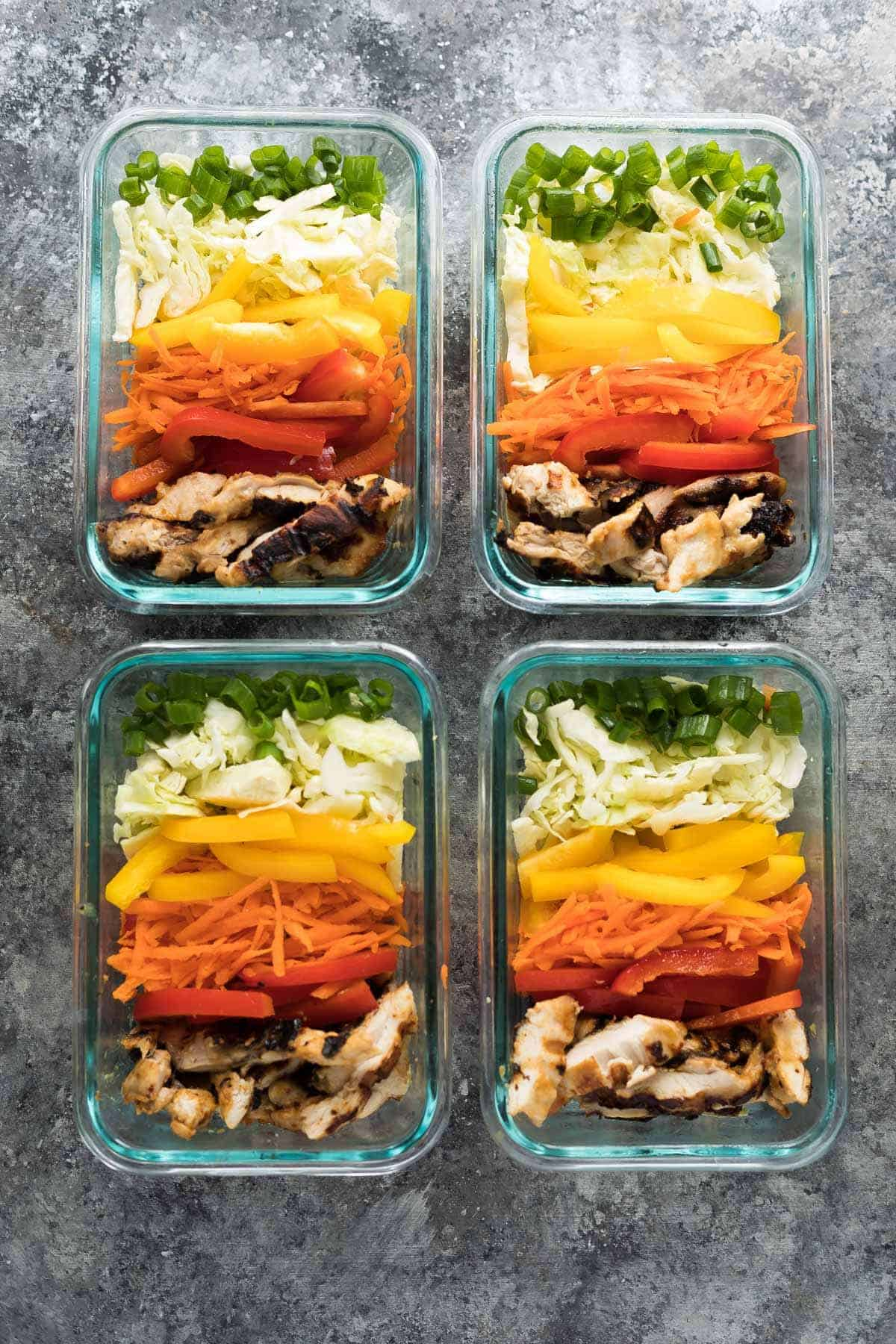 overhead shot of four satay chicken meal prep lunch bowls