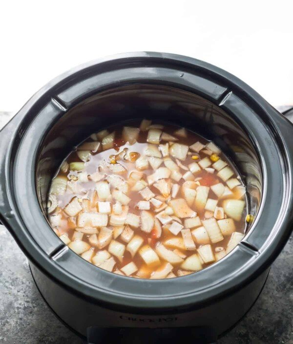 Slow cooker with broth and vegetables