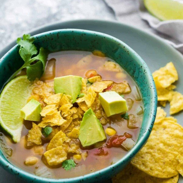 chickpea tortilla soup in blue bowl with tortilla chips, avocado slices and lime wedge