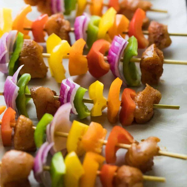fajita chicken skewers with onion peppers and chicken in a row