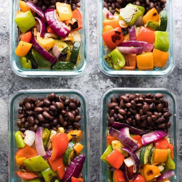 four glass meal prep containers filled with grilled veggie black bean meal prep bowls