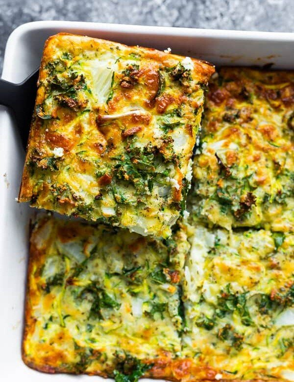 overhead shot of a slice of herb zucchini and kale egg bake being lifted out of the pan by a spatula