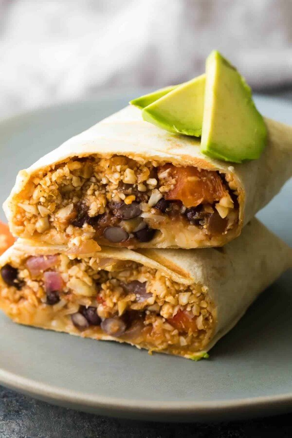 cauliflower rice black bean burrito cut in half and stacked on a plate with avocado slices